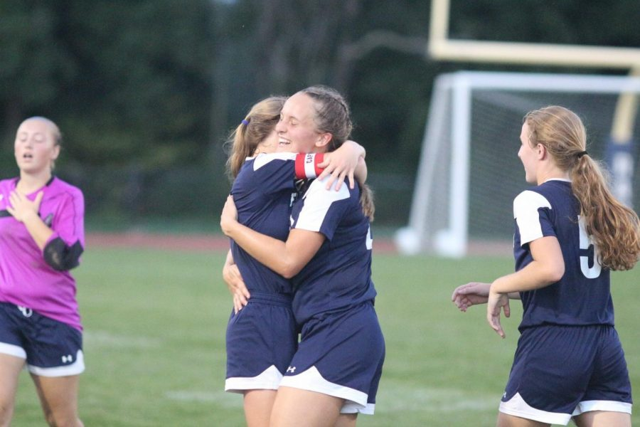 Previous player, Danae Hurd and returning player, Hannah Denger, hug after beating the 2017 Mountain League winners for the first time in years.