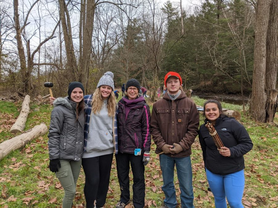 Outdoors Club members plant trees along the banks of Sinking Creek.