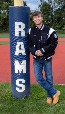 Seth Baney on the football field wearing his varsity jacket
