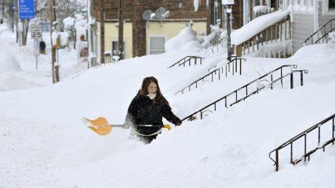 Women shoveling snow after snow storm.